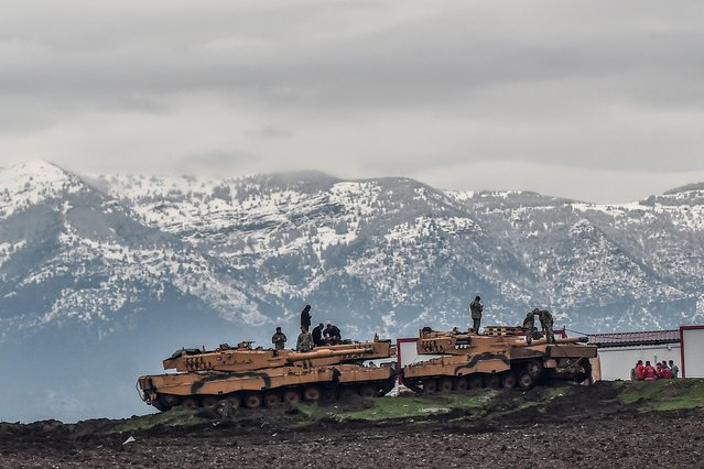 "Turkish tanks are parked near the Syrian border at Hassa, in Hatay province on January 24, 2018, as part of the operation ""Olive Branch"", launched a few days ago. The operation aims to oust the People's Protection Units (YPG) militia, which Turkey considers to be a terror group, from its enclave of Afrin. (Photo by Ozan Kose/AFP Photo)"