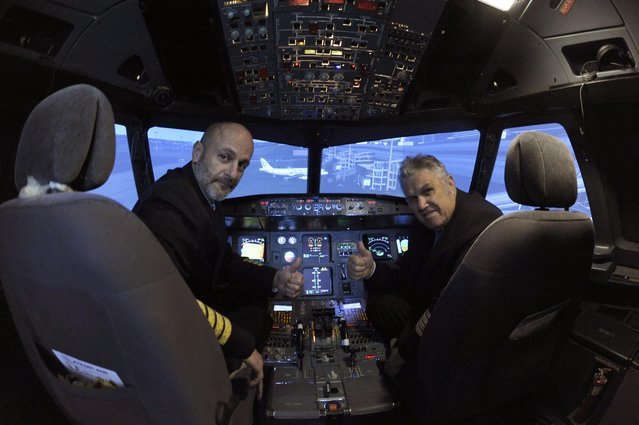 Igor Perne (L), 53, an electronic engineer and a member of the International Virtual Aviation Organisation (IVAO), and fellow virtual pilot Franc Lavric gesture for the camera before taking off on a virtual flight in a flight simulator in Nova Vas, Slovenia November 13, 2014. In 2011, Perne, a lifelong flying enthusiast, bought parts of a written-off Cyprus Airways airliner and then spent two and a half years turning the entire nose of the scrapped aircraft into an elaborate flight simulator. (Photo by Srdjan Zivulovic/Reuters)