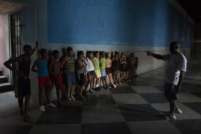 Children receive instructions from their wrestling teacher during a lesson in downtown Havana, October 20, 2014. (Photo by Alexandre Meneghini/Reuters)