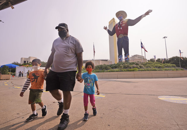 Wearing face masks to prevent the spread of COVD-19, Trey Lipscomb, center, holds the hands of his son, Trey, 6, and daughter Tia, 4, as they walk in front of Big Tex after getting their photo made during a visit to Fair Park in Dallas, Saturday, September 19, 2020. Although the State Fair of Texas was canceled this year, fair organizers are holding drive-thru visits starting this weekend. (Photo by L.M. Otero/AP Photo)