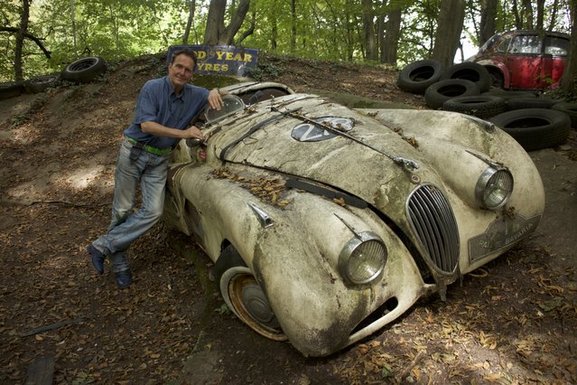 Michael stood next to his rotting Jaguar XK120 racecar that he used to win a grand prix in 1984 in Neandertal Germany, September 11, 2016. (Photo by Christoph Hagen/Barcroft Images)