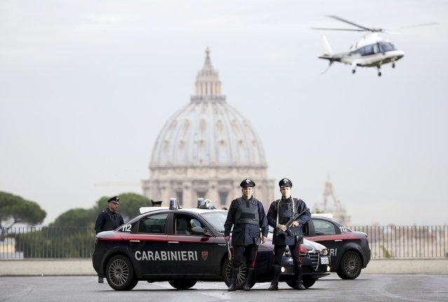 "Italian Carabinieri pose in front of St. Peter's Basilica as a Carabinieri helicopter flies overhead, in Rome November 12, 2014. In Italy, police and the paramilitary Carabinieri follow the same guidelines, which say that the use of weapons is allowed only in the line of duty, when it is an ""unavoidable necessity to overcome resistance, stop violence, or prevent a (serious) crime"", and that the response must be proportionate to the situation. (Photo by Alessandro Bianchi/Reuters)"