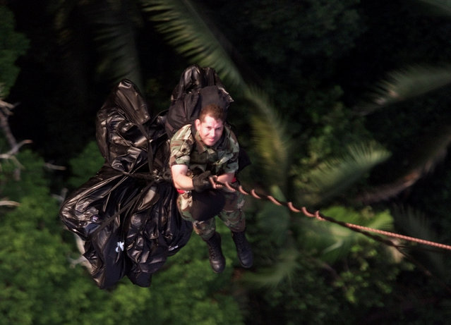 A Colombian soldier is carried by a Black Hawk helicopter in Puerto Siare, August 22, 2001. (Photo by Jose Gomez/Reuters)