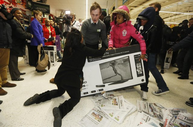 "Shoppers wrestle over a television as they compete to purchase retail items on ""Black Friday"" at an Asda superstore in Wembley, north London November 28, 2014. Britain's high streets, malls and online sites were awash with discounts on Friday as more retailers than ever embraced U.S.-style ""Black Friday"" promotions, seeking to kickstart trading in the key Christmas period. (Photo by Luke MacGregor/Reuters)"