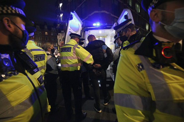 Police detain a man while dispersing a gathering in Soho on the last night before the city is put into Tier 2 restrictions to curb the spread of coronavirus, in London, Friday, October 16, 2020. (Photo by Jonathan Brady/PA Wire via AP Photo)