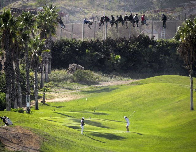 A golfer hits a tee shot as African migrants sit atop a border fence during an attempt to cross into Spanish territory, between Morocco and Spain's north African enclave of Melilla, in this October 22, 2014 file photo. (Photo by Jose Palazon/Reuters)