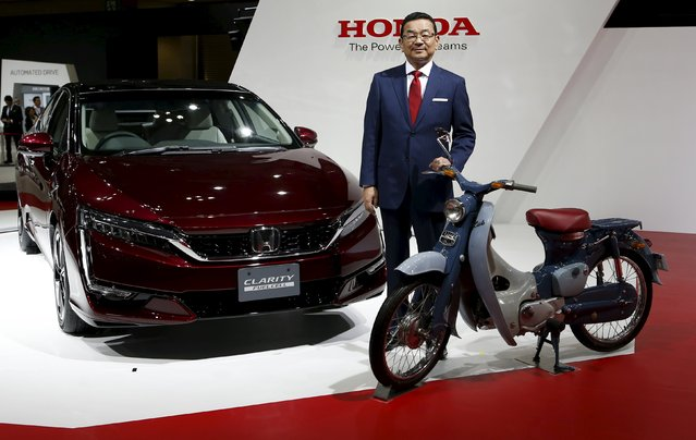 Honda Motor Co President and Chief Executive Takahiro Hachigo poses with its FCV Clarity Fuel Cell (L) and Super Cub Concept during a presentation at the 44th Tokyo Motor Show in Tokyo, Japan, October 28, 2015. Honda Motor Co is confident it can achieve its 2015 sales target of 950,000 cars in China, but is cautious about increasing production in the world's No.2 economy given the uncertain economic outlook, Hachigo told Reuters. (Photo by Yuya Shino/Reuters)