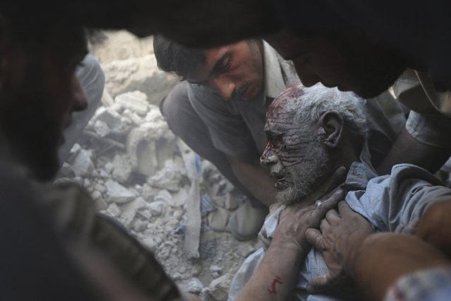 Residents carry an injured man out from the debris at a site hit by what activists claim were at least five air strikes by forces of Syria's President Bashar al-Assad in Douma, eastern al-Ghouta, near Damascus, in this September 11, 2014 file photo. (Photo by Bassam Khabieh/Reuters)