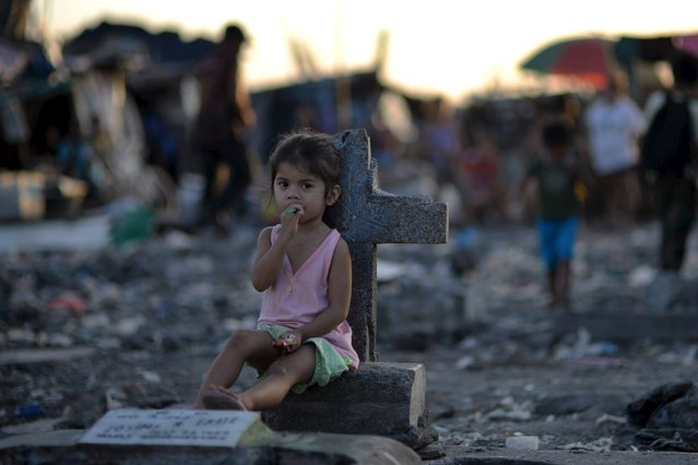 A girl sits next to a tombstone amidst a slum area inside the municipal cemetery in Navotas city, north of Manila October 29, 2015. (Photo by Ezra Acayan/Reuters)