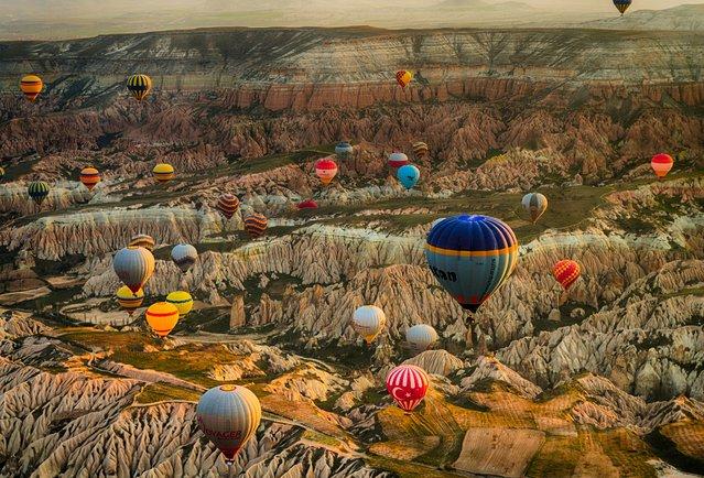 Dozens of rainbow-hued hot air balloons drift gently over a ragged mountainous region in Turkey. (Photo by Fatma Barla/500px)