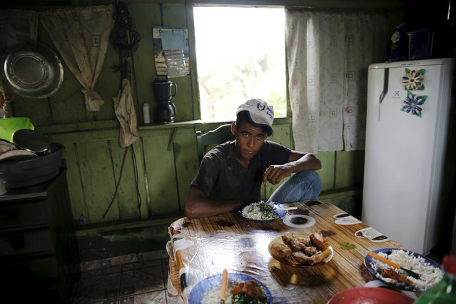 Roque sits at the table inside his house in the village of Rio Pardo next to Bom Futuro National Forest, in the district of Porto Velho, Rondonia State, Brazil, September 1, 2015. (Photo by Nacho Doce/Reuters)