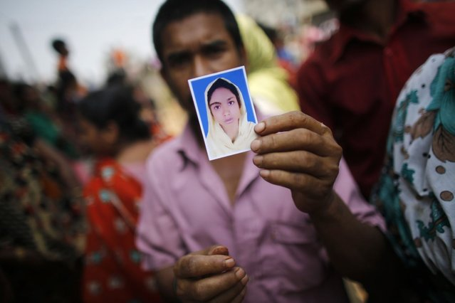 A relative holds a picture of a missing garment worker, who was working in the Rana Plaza building when it collapsed, in Savar, 30 km (19 miles) outside Dhaka April 24, 2013. The eight-storey block housing factories and a shopping centre collapsed on the outskirts of the Bangladeshi capital on Wednesday, killing more than 70 people and injuring hundreds, a government official said. (Photo by Andrew Biraj/Reuters)