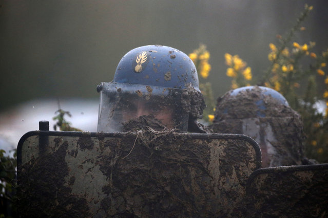 A French gendarme holds his mud-splattered shield during an evacuation operation in the zoned ZAD (Deferred Development Zone) in Notre-Dame-des-Landes, near Nantes, France, April 9, 2018. (Photo by Stephane Mahe/Reuters)
