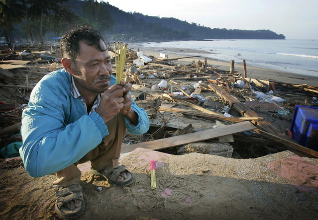 In this December 29, 2004 file photo, Kusol Wetchakul offers prayers for the soul of his sister, at dawn along the beach near Khao Lak, Thailand.  Wetchakul's sister was swept out to sea and believed drowned as she sold goods to tourists on the popular tourist beach just north of Phuket. (Photo by David Longstreath/AP Photo)