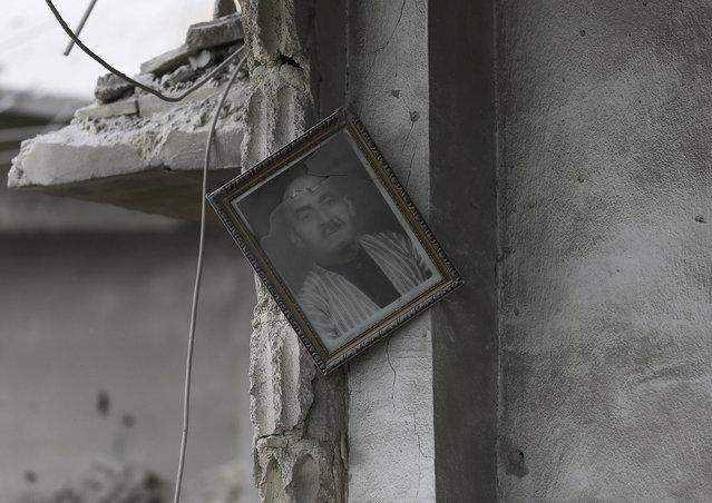 A framed portrait hangs off a wall inside a damaged house in Jobar, a suburb of Damascus, December 22, 2014. (Photo by Bassam Khabieh/Reuters)