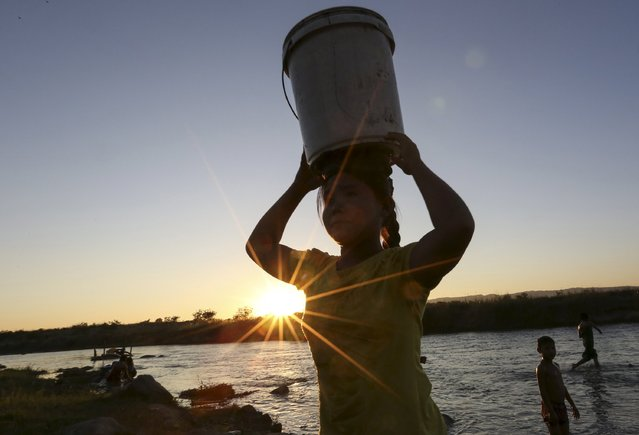 A girl carries a bucket of water on her head at a creek in Naypyitaw, Myanmar, November 14, 2015. (Photo by Soe Zeya Tun/Reuters)