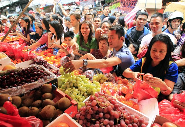 Holiday-goers choose fruits at a fruit market to buy assorted round shaped fruits in Manila December 30, 2014. Filipinos carry out a tradition of buying 12 different types of round fruits, each symbolising a month of the year, for good fortune for the coming New Year. (Photo by Romeo Ranoco/Reuters)