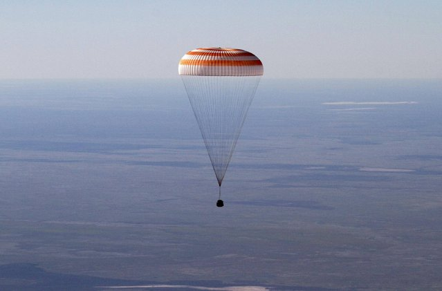 The Russian Soyuz space capsule, carrying U.S. astronaut Thomas Marshburn, Russian cosmonaut Roman Romanenko and Canadian astronaut Chris Hadfield, descends some 150 kilometers (94 miles) southeast of the town of Dzhezkazgan in central Kazakhstan, Tuesday, May 14, 2013. The Soyuz space capsule carrying a three-man crew returning from a five-month mission to the International Space Station landed safely Tuesday on the steppes of kazakhstan. (Photo by Sergei Remezov/AP Photo)