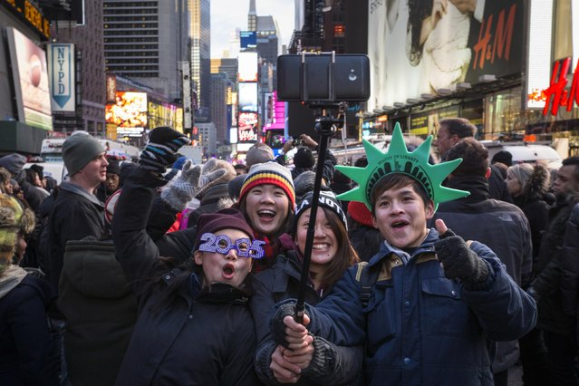 A boy (L) wears 2015 glasses as a group of family members use a selfie-stick to photograph themselves during New Year's Eve celebrations in Times Square, New York December 31, 2014. (Photo by Zoran Milich/Reuters)