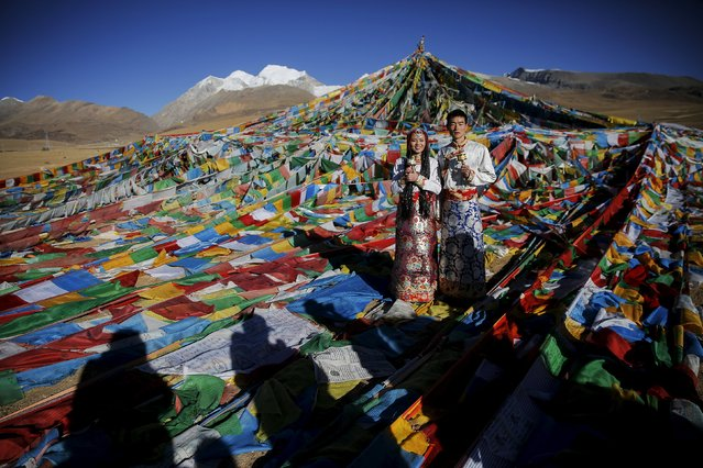 Jing Li (L) and her husband Ke Xu wear Tibetan traditional costumes as they pose for their wedding photos in front of Tibetan prayer flags at the Nianqing Tanggula mountain pass in the Tibet Autonomous Region, China November 18, 2015. Ke, 23, and Jing,22, both from Shiyan in northwestern Hubei province live in Tibet for three year. The couple married last month. (Photo by Damir Sagolj/Reuters)