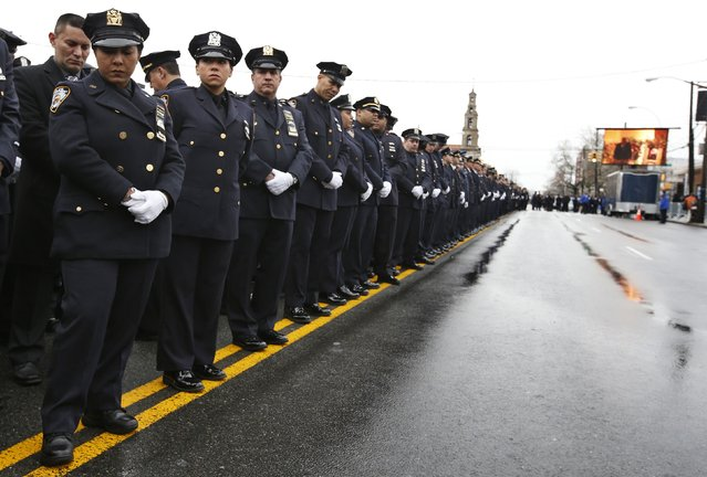 New York City police turn away from a screen showing New York Mayor Bill de Blasio speaking during the funeral service for New York Police Department officer Wenjian Liu in the Brooklyn borough of New York January 4, 2015. (Photo by Mike Segar/Reuters)