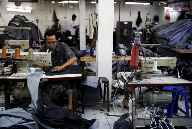 A worker stitches a pair of jeans at a small factory at Cakung industrial village in Jakarta, Indonesia, May 5, 2015. (Photo by Reuters/Beawiharta)