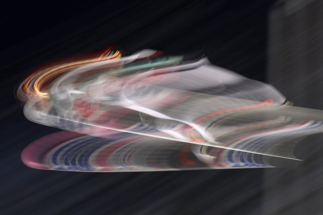 In this picture taken with a slow shutter speed, Junshiro Kobayashi of Japan soars through the air during a competition jump at the first stage of the 69th Four Hills ski jumping tournament in Oberstdorf, Germany, Tuesday, December 29, 2020. (Photo by Matthias Schrader/AP Photo)