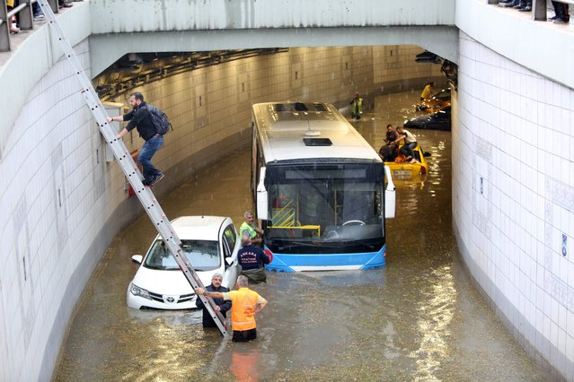People are evacuated from a flooded underpass following torrential rains in Ankara, on May 20, 2018. (Photo by Adem Altan/AFP Photo)