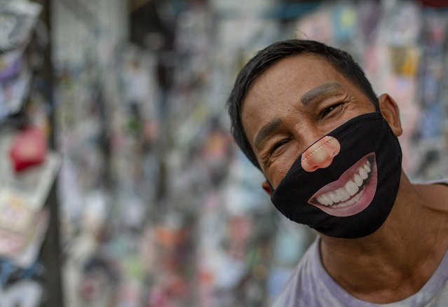 A mask seller wearing a mask stands in a street market in Bangkok, Thailand, Tuesday, June 9, 2020. Daily life in capital resuming to normal as Thai government continues to ease restrictions related to running business in capital Bangkok that were imposed weeks ago to combat the spread of COVID-19. (Photo by Gemunu Amarasinghe/AP Photo)