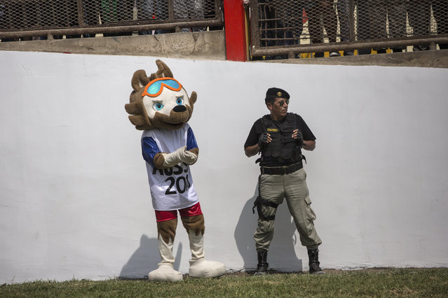 A prison guard stands next to an inmate dressed as the mascot of the Soccer World Cup Russia 2018, during a soccer match in the San Juan de Lurigancho prison, in Lima, Peru, Thursday, May 24, 2018. (Photoby Rodrigo Abd/AP Photo)