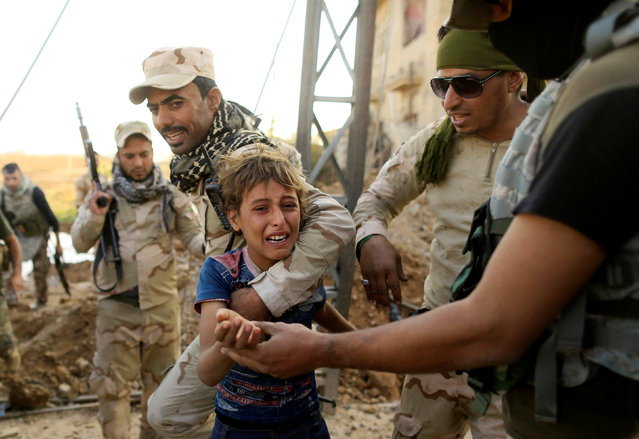 A boy reacts as Iraqi soldiers help him to walk out the front line during a battle with Islamic State in the Intisar disrict of eastern Mosul, Iraq November 4, 2016. (Photo by Zohra Bensemra/Reuters)