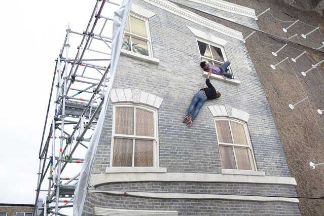"A person appears to be dangling as a large-scale installation art piece by Leandro Erlich, named ""Dalston House"", is displayed on June 24, 2013 in London, England. Part of the ""Beyond Barbican"" summer series of events, the interactive installation is a full facade of a late nineteenth-century Victorian terraced house built on the ground with a large mirror above it to reflect people as to appear dangling from the structure.  (Photo by Dan Dennison/Getty Images)"