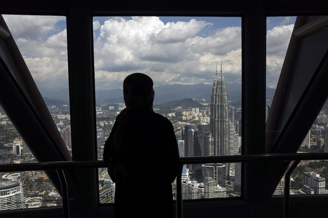 A woman is silhouetted against the Petronas Twin Towers as she has a souvenir photograph taken from the observatory deck of Kuala Lumpur Tower in Kuala Lumpur, Malaysia, Saturday, January 10, 2015. The Petronas Twin Towers is one of the major landmark in Kuala Lumpur city center alongside Kuala Lumpur Tower. (Photo by Joshua Paul/AP Photo)