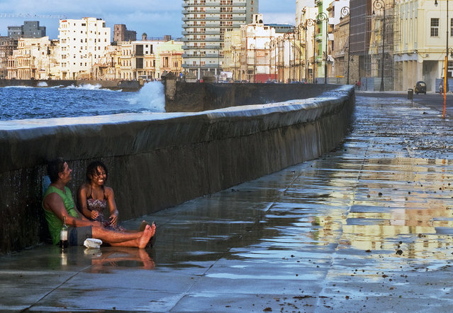 """Fun on the Malecon"". While strolling down the Malecon in Havana, Cuba, I came across this couple. They were laughing and drinking and getting soaked by an occasional wave that broke over the sea wall. They were oblivious to the rest of the world while they enjoyed each other immensely. (Photo and caption by Jim Tardio/National Geographic Traveler Photo Contest)"