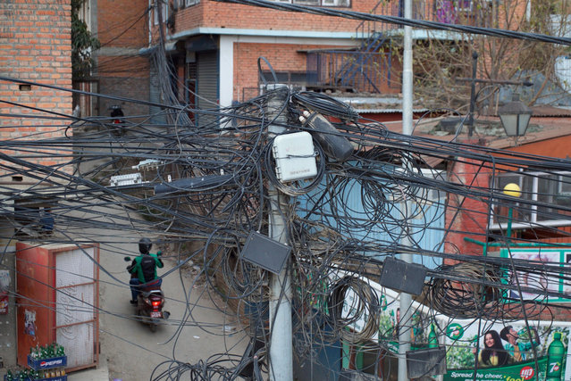 Kathmandu's chaotic electrical wiring has further hampered road expansion. As roads have been widened the electricity poles have also had to be moved, but a lack of co-ordination between the roads and electricity departments has held up progress. (Photo by Pete Pattisson/The Guardian)