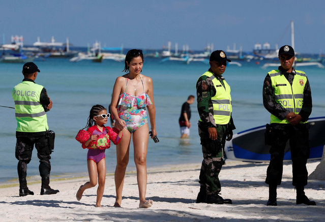 Tourists walk past policemen, one day before the temporary closure of the holiday island Boracay, in the Philippines April 25, 2018. (Photo by Erik De Castro/Reuters)