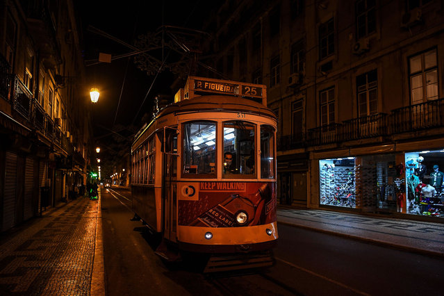 An empty tram drives through an empty street in downtown Lisbon on November 9, 2020. Portugal introduced a curfew across most of the country in an effort to combat surging case numbers. (Photo by Patricia de Melo Moreira/AFP Photo)