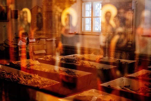 A picture taken on February 8, 2021 shows coffins with remains of Russian and French soldiers who died during Napoleon's 1812 retreat, reflected in an Orthodox icon during a ceremony in a small church in the monastery of John the Precursor in the town of Viazma. The remains of a hundred Russian and French soldiers, unearthed in Viazma, a small town in western Russia, will be buried together on February 13, 2021. (Photo by Dimitar Dilkoff/AFP Photo)