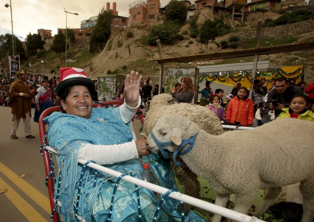 An Aymara woman with a sheep waves to the crowd during a Christmas parade in La Paz, Bolivia December 12, 2015. (Photo by David Mercado/Reuters)
