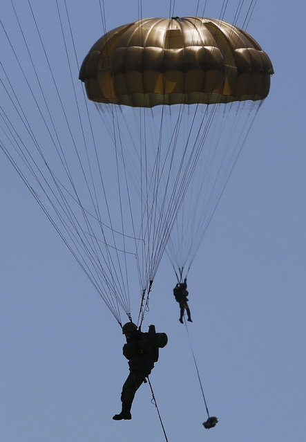 Japanese Ground Self-Defense Force's 1st Airborne Brigade soldiers parachutes down from a CH-47 helicopter during their military drill at Higashifuji training field in Susono, west of Tokyo, July 8, 2013. Japan faces increasingly serious threats to its security from an assertive China and an unpredictable North Korea, a defence ministry report said on Tuesday, as ruling politicians call for the military to beef up its ability to respond to such threats. (Photo by Issei Kato/Reuters)