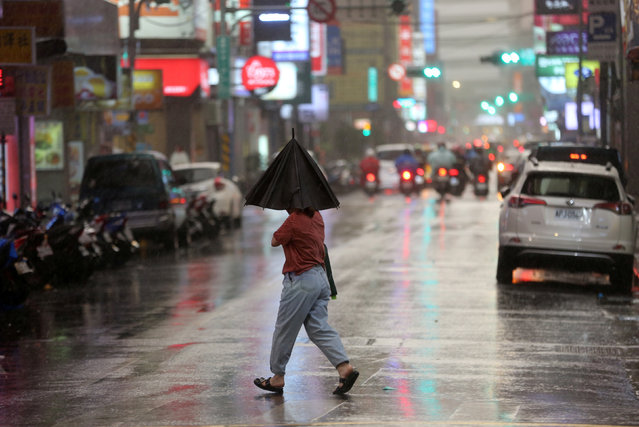 A person braves strong winds while crossing a street in Taipei as Taiwan braced for super typhoon Maria on July 10, 2018. (Photo by Eason Lam/Reuters)