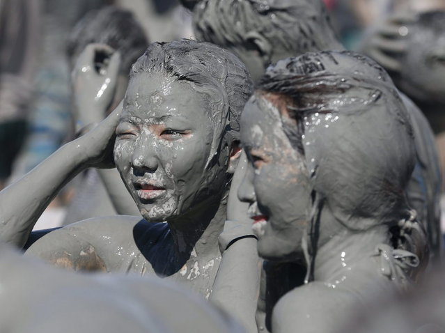 Tourists play in the mud during the Boryeong Mud Festival at Daecheon beach in Boryeong, about 190 km (118 miles) southwest of Seoul, July 19, 2013. About 2 to 3 million domestic and international tourists visit the beach during the annual mud festival, according to the festival organisers. (Photo by Lee Jae-Won/Reuters)