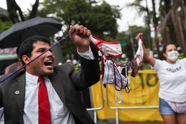 Supporters of Brazil's President Jair Bolsonaro hold a string of underwear to mock Governor of Sao Paulo Joao Doria during a protest against the measures he implemented to curb the spread of the coronavirus disease (COVID-19), in Sao Paulo, Brazil, March 7, 2021. (Photo by Amanda Perobelli/Reuters)