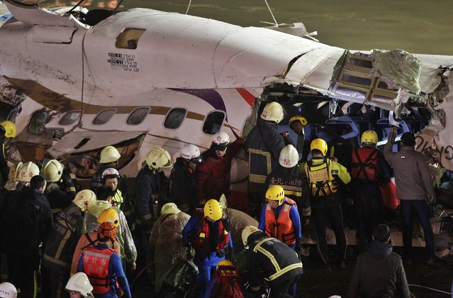 Rescuers search inside the wreckage of a TransAsia Airways turboprop ATR 72-600 aircraft after it was recovered from a river, in New Taipei City, February 4, 2015. (Photo by Pichi Chuang/Reuters)