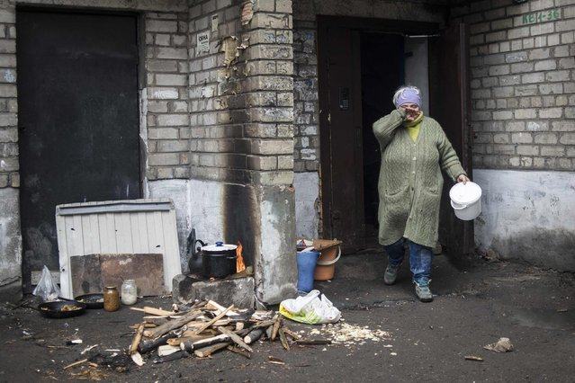A woman walks to cook on a fire outside her house in Debaltseve, February 3, 2015. (Photo by Sergey Polezhaka/Reuters)