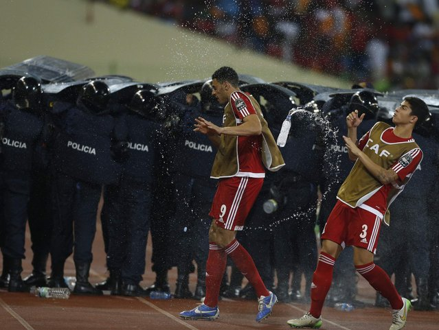 Equatorial Guinea's players dodge water bottles thrown by fans as police protect Ghana players during their semi-final soccer match of the 2015 African Cup of Nations in Malabo, February 5, 2015. (Photo by Amr Abdallah Dalsh/Reuters)