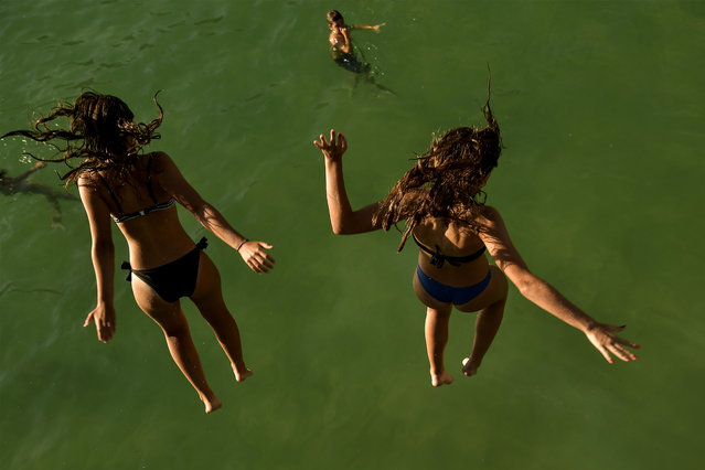 Two women jump from a platform over the water at La Concha beach during a hot summer day in the basque city of San Sebastian, northern Spain, Friday, August 3, 2018. Hot air from Africa is bringing a heat wave to Europe, prompting health warnings about Sahara Desert dust and exceptionally high temperatures that could peak at 47 degrees Celsius (117 Fahrenheit) in Spain and Portugal. (Photo by Alvaro Barrientos/AP Photo)