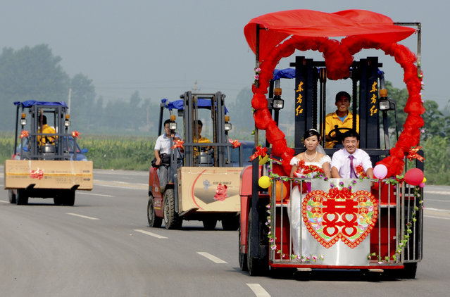 Bridegroom Kong Qingyang and his bride Shen Likun sit on a forklift, which is transformed into a wedding car, during their wedding in Xingtai, Hebei province, August 3, 2011. Kong, a former forklift driver, met his bride Shen, who was a forklift seller, while buying a forklift from her. Picture taken August 3, 2011. (Photo by Reuters/China Daily)