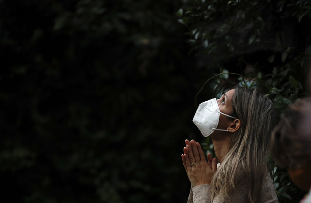 A woman attends Mass outside the Schoenstatt shrine during Easter in Buenos Aires, Argentina, Thursday, April 1, 2021. The Mass was held outside to avoid the spreading of COVID-19. (Photo by Natacha Pisarenko/AP Photo)