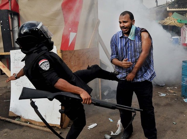 A policeman kicks a supporter of ousted Islamist President Mohammed Morsi as they clear a sit-in camp set up near Cairo University in Cairo's Giza district, on August 14, 2013. (Photo by Hussein Tallal/Associated Press)